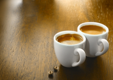 Two cups of freshly brewed espresso coffee with two single coffee beans on a textured wooden table top with copyspace photo