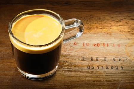 High angle view of a refreshing glass mug of strong frothy espresso coffee on a grunge wooden background with numbers stamped into the wood photo