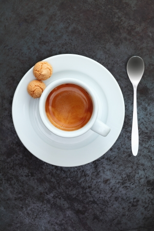 frothy: Overhead view of strong frothy espresso coffee in a cup and saucer with two traditional macaroons and a silver teaspoon Stock Photo