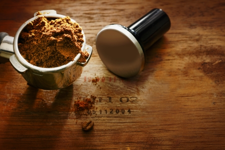 tamper: Freshly ground coffee beans in a metal filter on a wooden background with copyspace during preparation of a cup of aromatic filter coffee or espresso Stock Photo