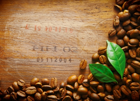 coffee grounds: Coffee bean border on an old wood surface with stamped numbers from a shipment of coffee beans with two green leaves Stock Photo