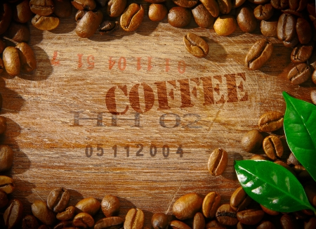 Fresh roasted coffee beans framing an old wooden board stamped with the word COFFEE and the shipment number of a consignment of beans with two fresh green leaves in the corner photo