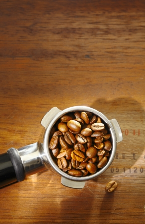 Overhead view of fresh roasted coffee beans in an espresso filter on a textured wooden surface with copyspace photo