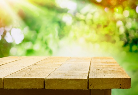 tabulka: Prázdný dřevěný stůl se zahradním bokeh pro catering nebo potravin pozadí s country venkovním téma