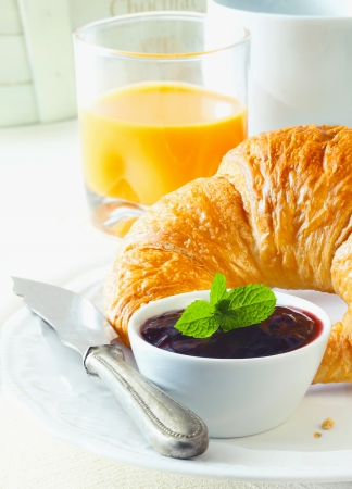 Sain petit déjeuner continental avec un croissant au beurre fraîchement cuit croustillant et un pot de confiture accompagné d'un verre de jus d'orange frais