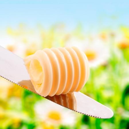 mantequilla: Curl de mantequilla fresca en verano en un rollo en espiral en equilibrio sobre un cuchillo de plata al aire libre, bajo el sol de verano con vegetación