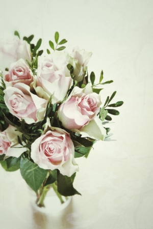 High angle view of a fresh bouquet of delicate pink roses arranged with foliage in a glass vase over a white background with copyspace Stock Photo - 17322850