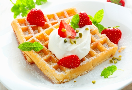 waffle: Golden waffle topped with fresh sliced strawberries and cream and sprinkled with sugar for a delicious dessert