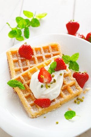 sou: Crisp golden waffles, strawberries and cream garnished with fresh mint and sprinkled with sugar for a delicious summer dessert
