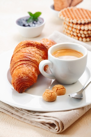 Freshly baked crisp golden croissant served with a cup of rich espresso and two small macaroon biscuits in a restaurant
