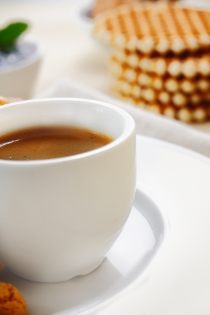 Cropped closeup view of a plain white ceramic cup filled with rich strong espresso coffee served with waffles for breakfast photo