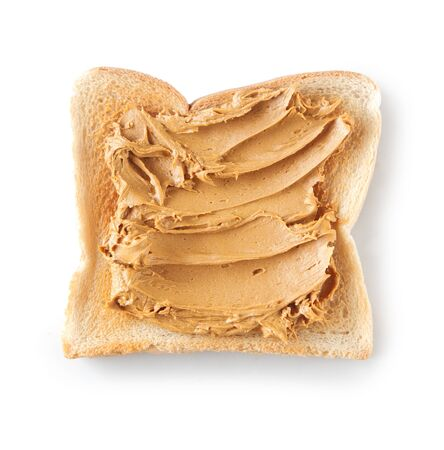 peanut butter: Slice of tasted white bread with a generous topping of delicious nutty smooth peanut butter on a white background Stock Photo