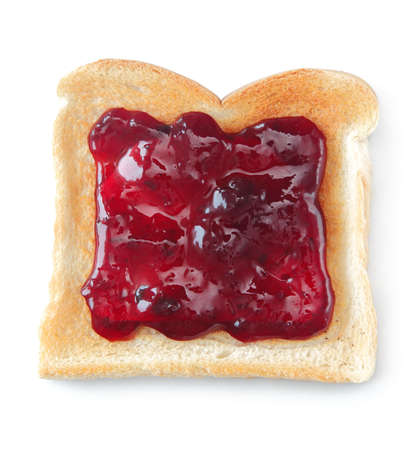 sweet and savoury: Slice of toast on a white background, made from white bread a liberally coated with a red berry jam Stock Photo