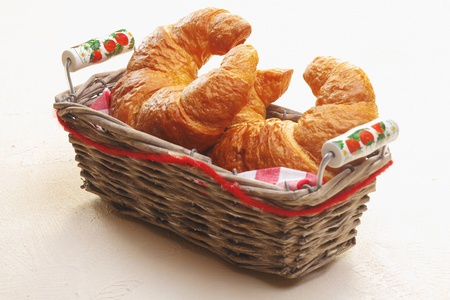 freshly: Basket of freshly baked golden crescent-shaped croissants on a white tabletop to serve as an accompaniment to a meal Stock Photo
