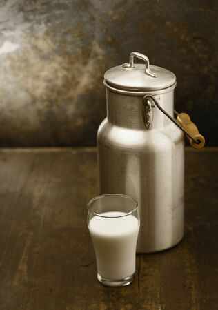 Metal milk can with a glass of fresh milk standing together on an old rustic wooden table in front of a grungy stained wall photo