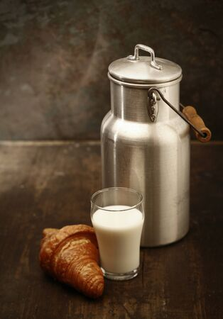 Healthy fresh milk for breakfast in a tall tumbler freshly dispensed from the metal milk can and served with a crisp golden croissant in a rustic kitchen photo