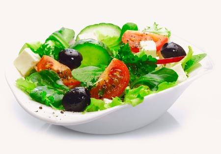 green salad: Individual side serving of delicious fresh Greek salad with feta cheese, olives, tomatoes and salad greens Stock Photo