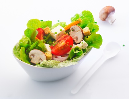 Individual side serving in a white china dish of fresh mixed green salad with sliced fresh mushrooms , tomato and feta cheese