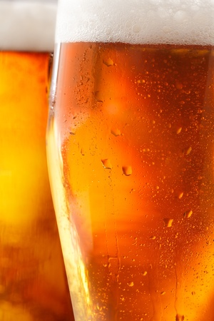 carbonated: Cropped closeup of a glass of cold beer with a frothy head and water droplets from condensation beading the outside of the glass Stock Photo