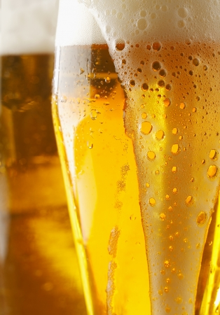 beer foam: Closeup of a frothy cverflowing glass of golden ale or beer with liquid running down the outside of the glass, cropped view image Stock Photo