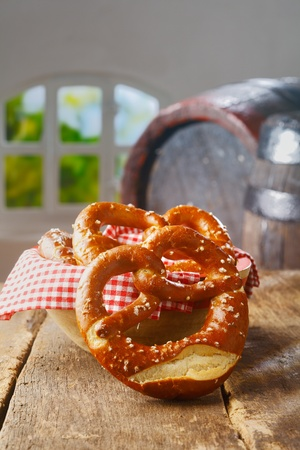 Crisp golden knot-shaped pretzels on a wooden table with an old vintage oak barrel and summery window behind photo