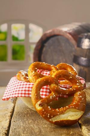 pretzels: Crisp salty golden-brown pretzels served as a savoury snack in a pub or restaurant with an old wine barrel visible behind