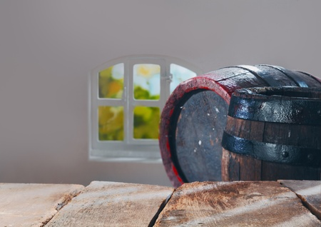 Old stained vintage wooden oak beer or wine barrels behind an empty rustic wood table as a background for your food or beverage concept photo