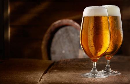 cerveza: Dos vasos de cerveza espumosa fresca sobre una mesa en una bodega de cerveza del vintage con un barril en el fondo Foto de archivo