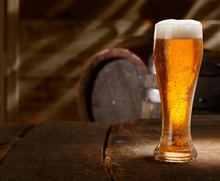 vasos de cerveza: Primer plano de un vaso de cerveza espumosa fresca sobre una mesa en una bodega de cerveza vendimia Foto de archivo