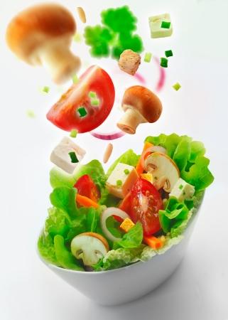 accompagnement: Bol c�t� individuel de sant� salade verte mixte de la laitue, la carotte, l'oignon, les champignons, les tomates et feta avec des ingr�dients suppl�mentaires dans l'air �me recul dans la distance sur un fond blanc Banque d'images