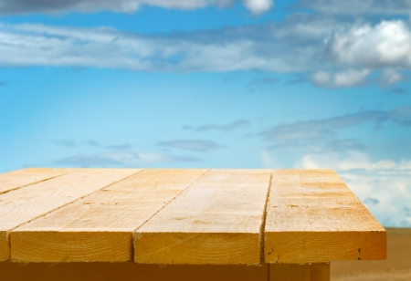 Empty wooden table top against a blue sky with fluffy white clouds for the placement of your food or product