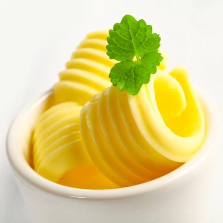 圧延ゴールデン バター デザイナー イベントの仕出し料理のスライスまたはレストランでミントを添えて小さなセラミック皿の浅いと dof のクローズ 写真素材