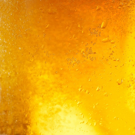 chilled: A background created from a closeup of cold light beer in a glass, with condensation droplets on the outside of the glass