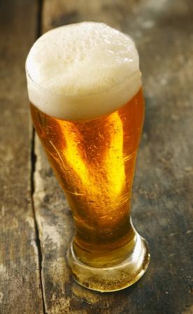 frothy: Alto angolo di vista di un bicchiere di birra fresca con una testa schiumoso in piedi su un vecchio tavolo di legno del grunge
