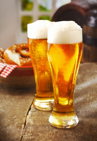draught: Two tall glasses of golden ale or beer with a good head of white froth on an old wooden kitchen table with a basket of rolls behind