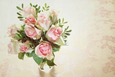 High angle view of a bunch of delicate fragrant fresh pink roses arranged in a glass vase with greenery and copyspace photo