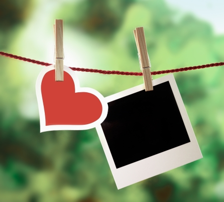 memories: Romantic Valentine memories and greeting card with a pretty white-bordered red heart hanging on an outdoor line with a blank instant photo frame for your image or message