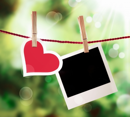 wedding photo frame: Romantic Valentine or anniversary card with a fresh red heart hanging on a line outdoors alongside an empty instant photo frame bathed in ethereal golden sunlight for those special memories Stock Photo