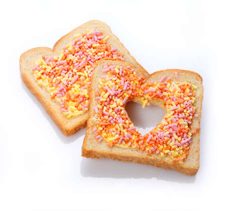 Elegant dessert made of slices of bread with candies having cut the shape of a heart photo