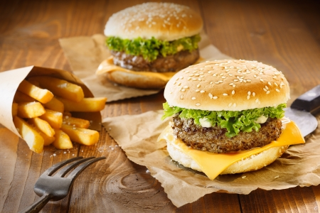 burger bun: Two hamburger and fries on brown paper and wooden table
