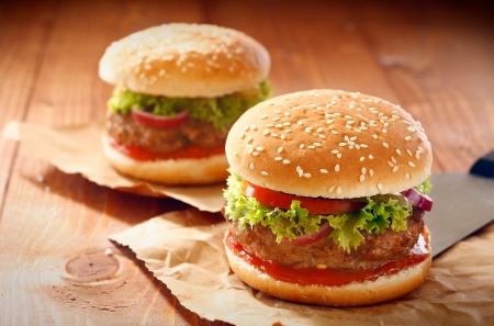 comida chatarra: Dos hamburguesas y papas fritas franc�s con s�samo bollo de papel marr�n