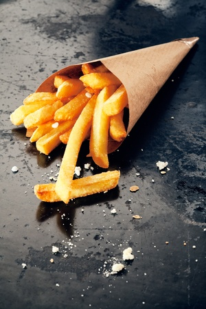 Hot salty fried potatoes in a paper cornet, close up Banco de Imagens