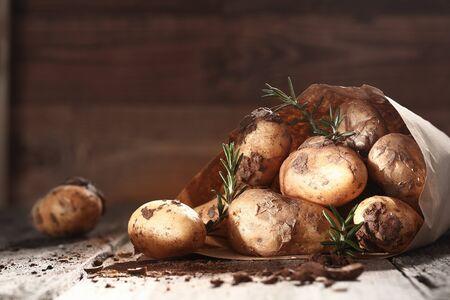 unwashed: Fattoria patate fresche non lavate con rametti di rosmarino fresco spillijng fuori da un sacchetto di carta marrone su un tavolo di legno in un mercato degli agricoltori