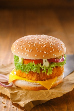 Delicious chicken burger with a golden crumbed patty and salad ingredients on grungy crumpled brown paper against a wooden backdrop with copyspace photo