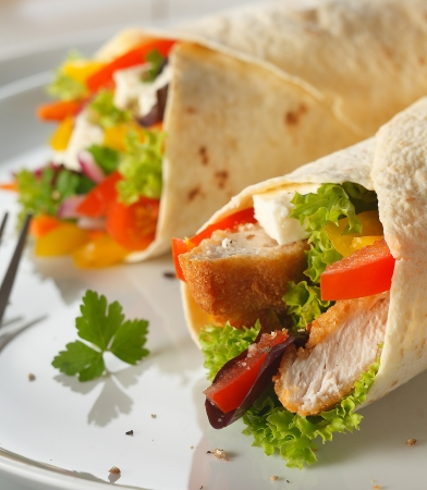 wrap: Delicious vegetarian pancake wraps filled with feta cheese, salad and crusty bread chunks, closeup view on a plate
