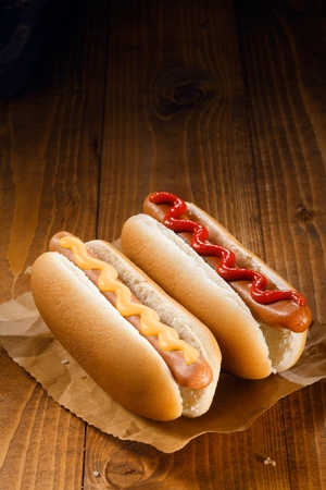 Two hotdogs, one with ketchup, one with mustard on wooden background photo