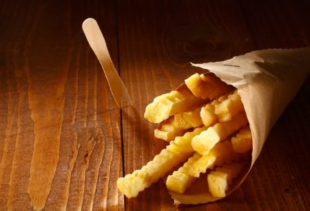 Crinkle cut golden french fries served as a takeaway in a roll of brown paper lying on a wooden table with copyspace photo