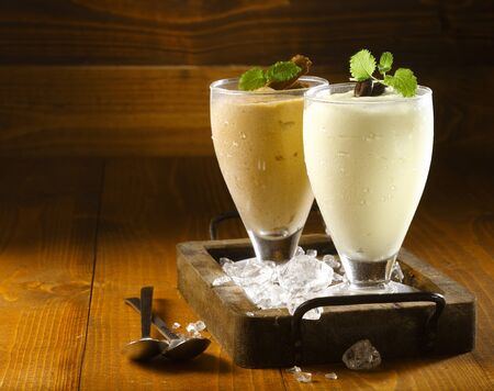 milkshake: Two delicious thick icecream milkshakes garnished with chocolate and mint and served in tall chilled glasses on a small old wooden tray