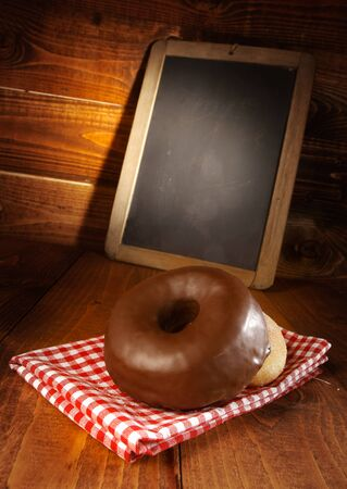 Fresh delicious chocolate doughnut displayed on a red and white checked napkin on a wooden surface in front of a small blank chalkboard for your menu, price or recipe Stock Photo - 17853268