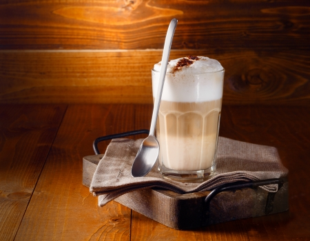 Delicious layered cappuccino or latte macchiato coffee served in a long glass with a spoon against a rustic wooden background with copyspace